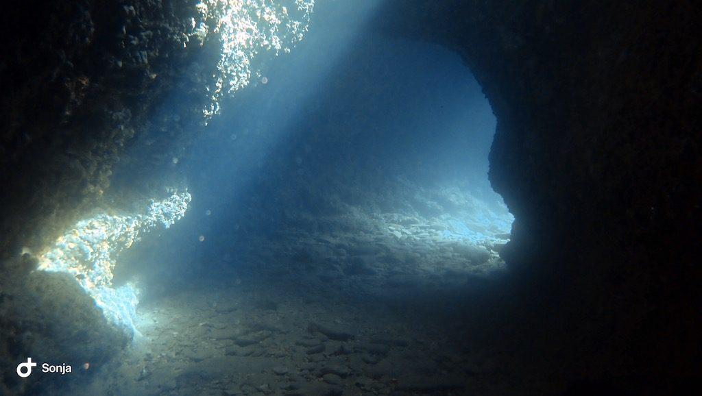 Licht faellt in eine Hoehle unterwasser