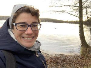 Frau am See, die in Kamera lächelt.