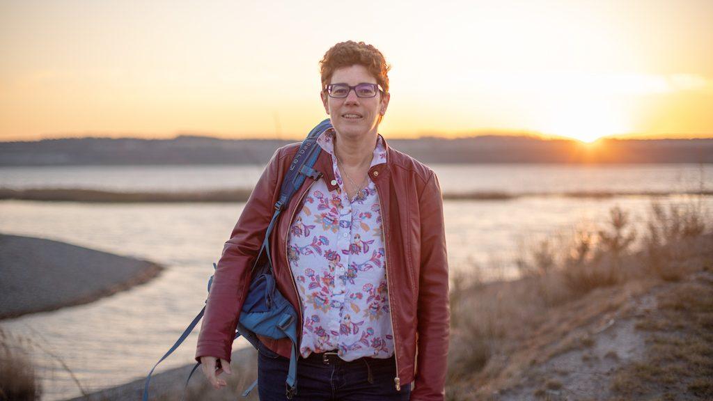 Frau mit Rucksack vor See und Sonnenschein