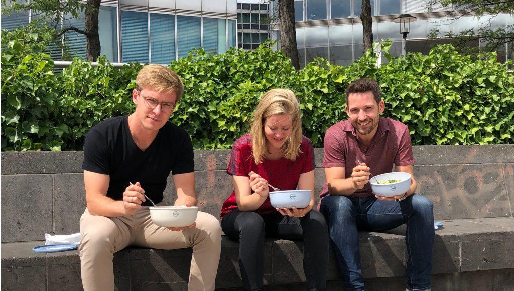 Bild mit drei Leuten sitzen zum Mittagessen auf Bank mit VYTAL Bowls