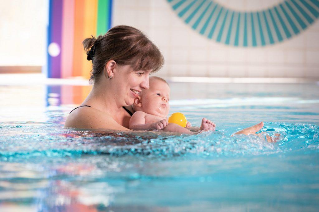 Mutter und Baby beim Planschen im Wasser