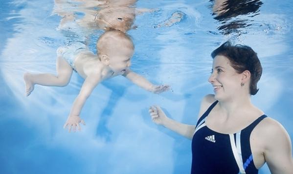 Baby schwimmt zur Mutter unter Wasser