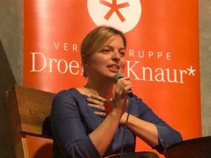 Katharine Schule vor Plakat von DroemerKnaur