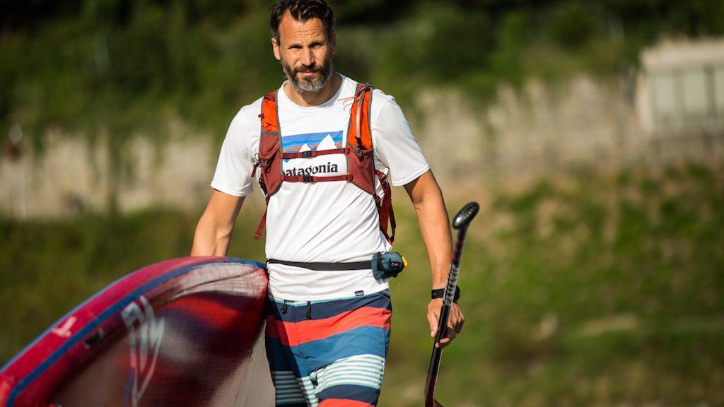Pascal Rösler mit SUP Board auf dem Weg zum Wasser