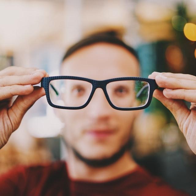 Mann hält Brille hoch