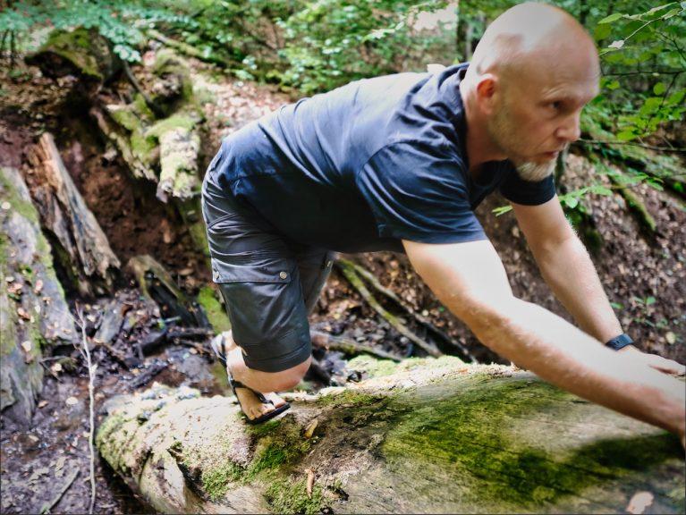 Mann klettert auf Baumstamm